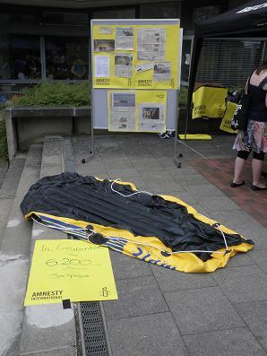 Ein luftloses Schlauchboot liegt am Boden. Dahinter eine Info-Wand zum Thema Flüchtlingsschutz.