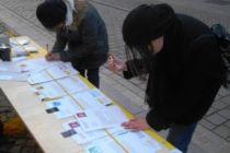 Menschen unterschreiben Petitionen an einem Stand zum Briefmarathon in der Fußgängerzone.